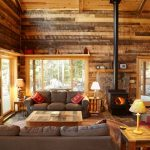 rustic mud wood interior living room door lamp sofa pillow wooden walls fireplace carpet hardwood floor table shelf window