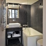 Small Bathroom With Black Mosaic Tiles On Wall And Sink, Grey Tiles Flooring, White Bathtub Sink And Toilet, Metal Rack