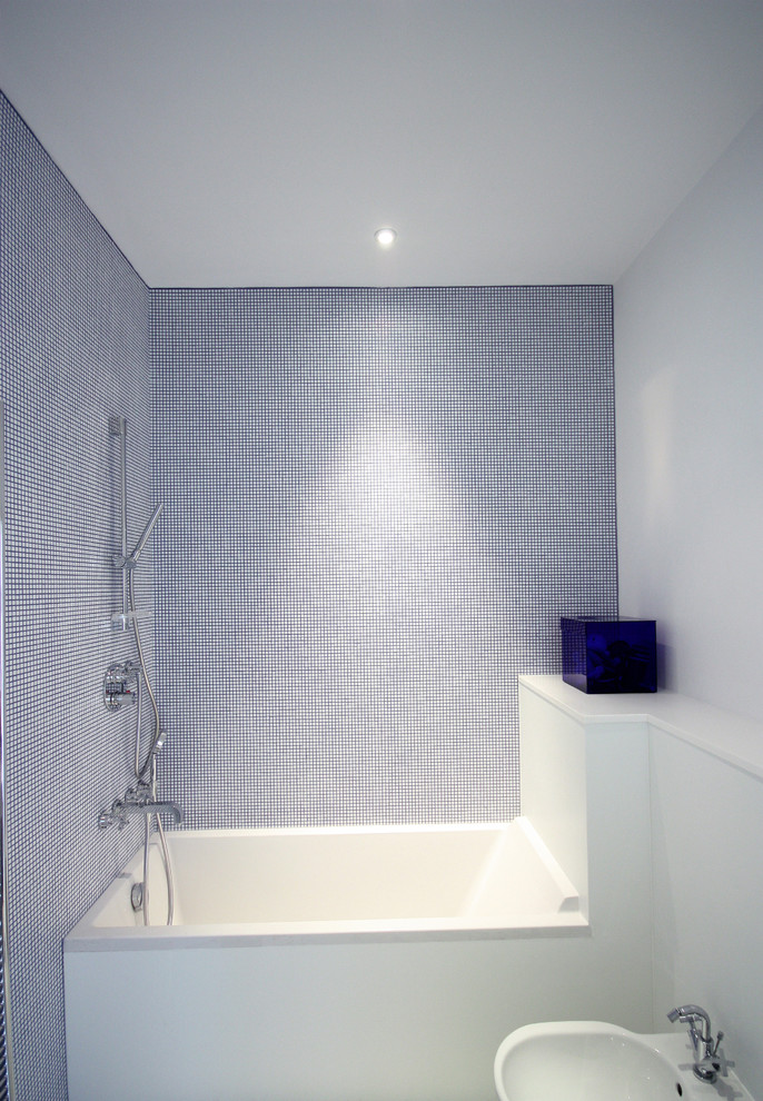 small bathroom with mosaic tiles on the wall, white square tub, white toilet