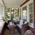 Sunroom With Window Seating Area With White Cuhion, Rattan Chairs And Coffee Table With Stripped Cushion, Brown Rug