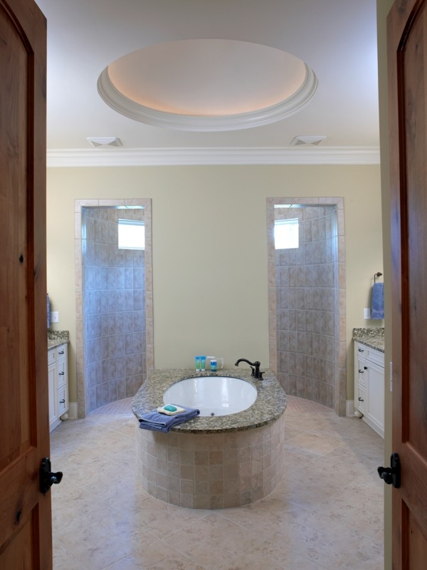 symmetrical walk in showers white cabinets round white tub bronze tap cream tiles marble countertops cream wall paint