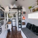 Tiny House Trailer With Bedrooms In The Attic, Black Sofa, Small Kitchen With Oven And Refrigerator, TV, Bathroom Under The Bedrom