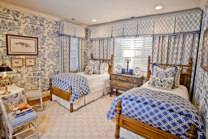 traditional bedroom with blue white wall paper, white flooring, two single brown wooden bedding, blue white bed cover, side table, curtain, table chairs