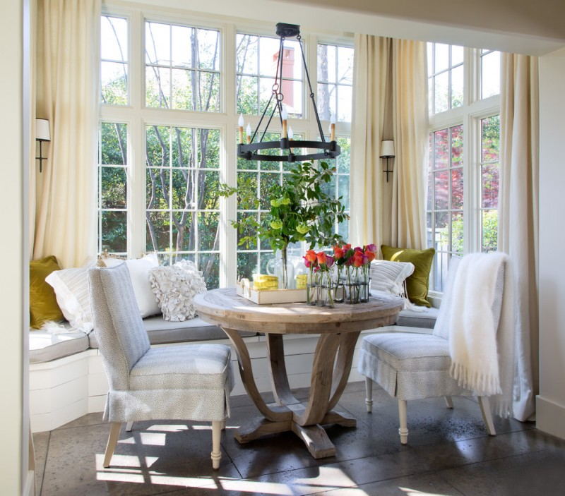 traditional dining nooks with pillow throws round table and grey chairs grey tiles floor glass framed windows pendant lamp