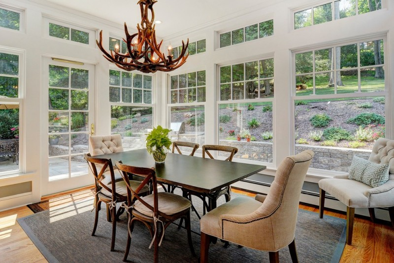 traditional dining room bright colour schemes big windows chairs table pillows hardwood floor carpet chandelier