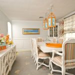traditional dining room bright colour schemes carpet window curtains flowers painting hanging lamps chairs table white orange cabinet