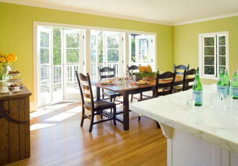 traditional dining room bright colour schemes flowers window chairs table three doors light green brown white