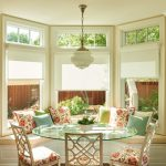 traditional dining room bright colour schemes glass top table chairs white walls pillows windows