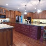 Traditional Kitchen Model With Purple Kitchen Island Dark Wood Floors Dark Finished Wood Cabinets White Backsplash Stainless Steel Appliances Grey Stools