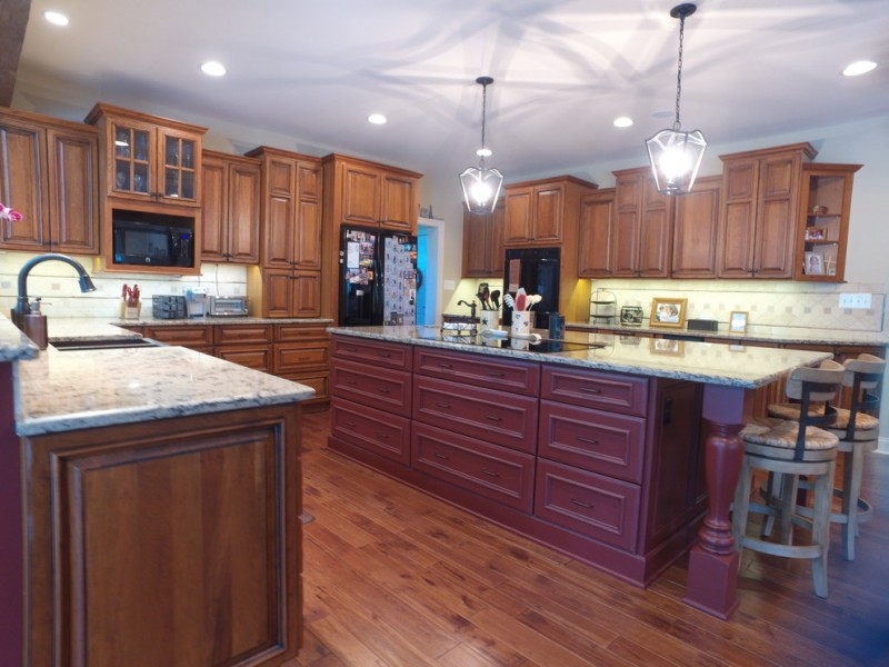 traditional kitchen model with purple kitchen island dark wood floors dark finished wood cabinets white backsplash stainless steel appliances grey stools
