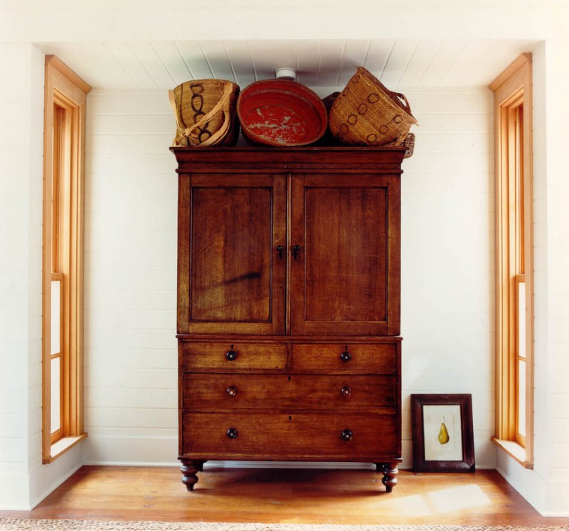 traditional wood cupboard in dark toned wood color medium toned wood floors clean white walls white siding wood ceiling