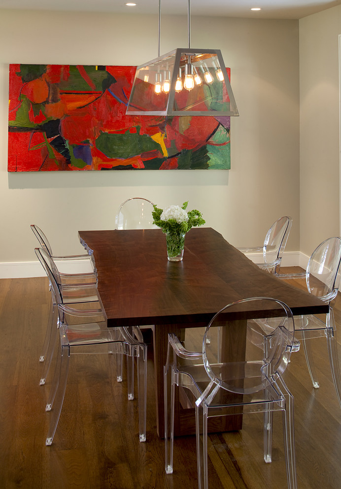 tree cut dining table clear acrylic dining chairs dark toned wood floors colorful abstract painting