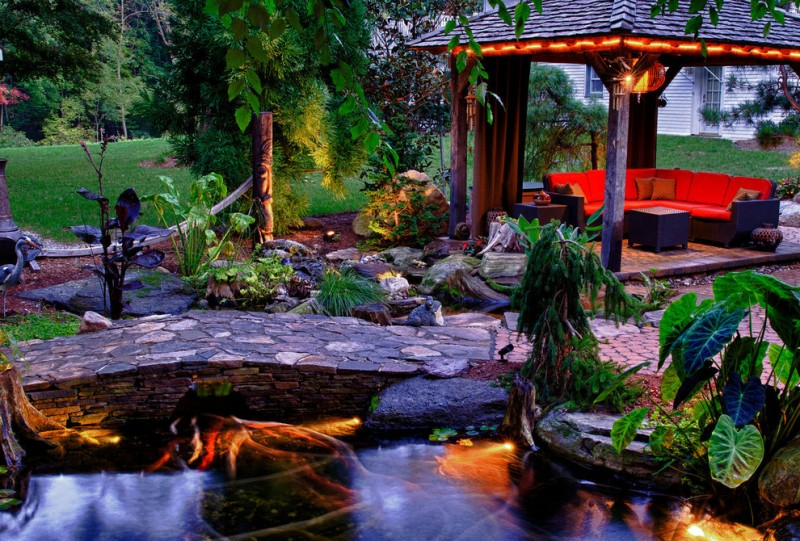 tropical landscape yard with gazebo, red sofa, stone bridge, lightings under the plants