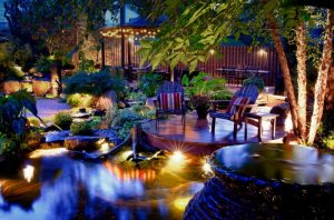 tropical yard with wooden deck, stone flooring, yellow lighting under the plants and the deck, gazebo with hanging lighting