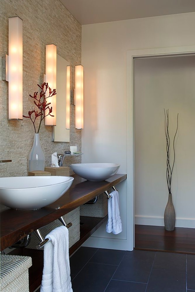 two white bowl sinks sitting on wooden vanity with towel rack under it