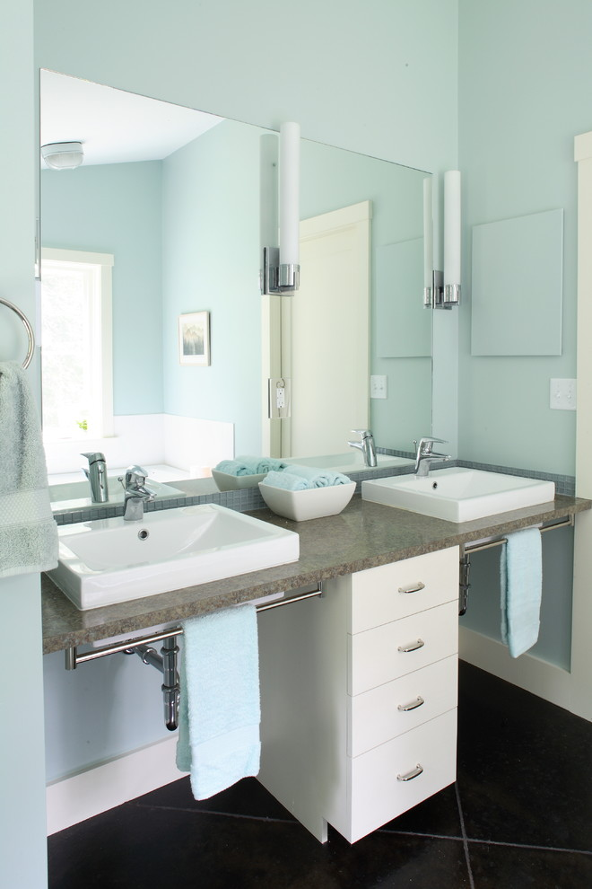 two white sinks with brown marble vanity, towel rack under the vanity