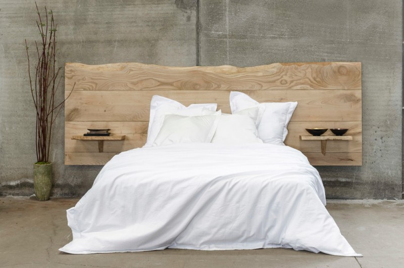 unique wood bed design with extra large headboard and mounted side tables full cover white duvet and white pillows concrete walls and floors