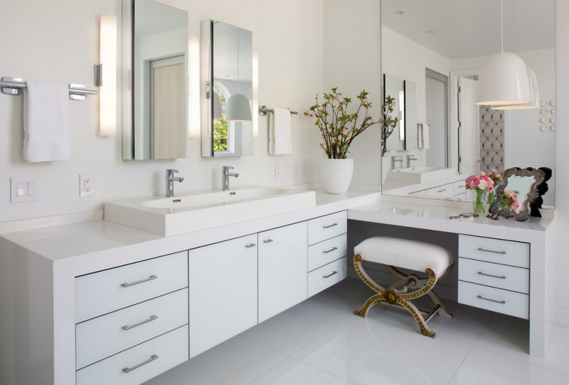 white bathroom with white ceiling, wall, flooring, L shaped vanity with white cabinet under, white double adjoint sink, three mirrors, sconces