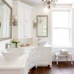 white bathroom with white wall and ceiling, white vanity, chandelier, wooden flooring, mirror, sconces