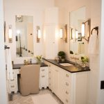 white bathroom with white wall, cabinetery, black soapstone top, tile flooring, mirror, sconces