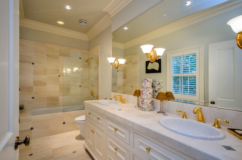 white bathtub with brown tiles outside and in the wall and golden shower installed against the wall inside