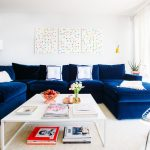 white coffee table navy blue velvet sofa mosaic wall decoration cream rug white walls magazines and books