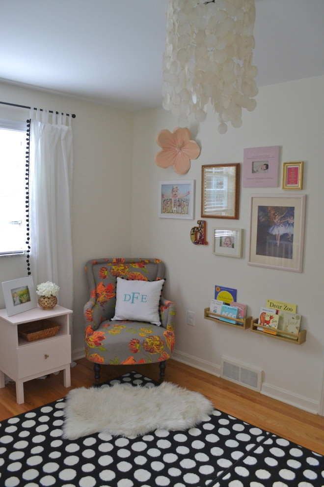 white painted walls with memorial pictures grey armchair with dazzling flower motifs polka dots area rug white fluffy mat under chair small & white side table a couple of wood floating shelves