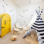 White Walls With Decorative Black Arrows Prints Lower And Smaller Yellow Entrance Door A Set Of White Fluffy Chairs With White Round Top Table Kids' Monochromatic Tent With Under White Fluffy Rug