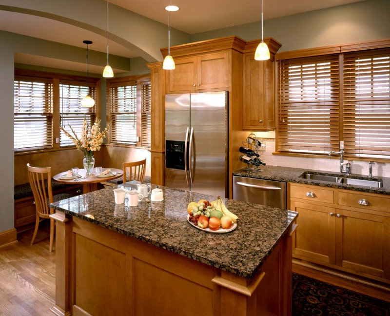 wood island wood cabinet brown granite countertop stainless steel appliances pendant lights