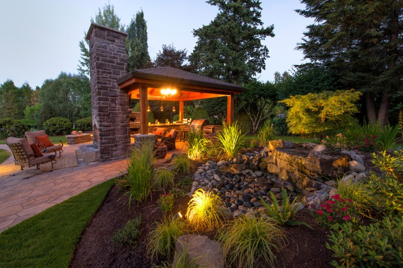 yard with lots of plants, gazebo with stoney chimney, lighting on the plants