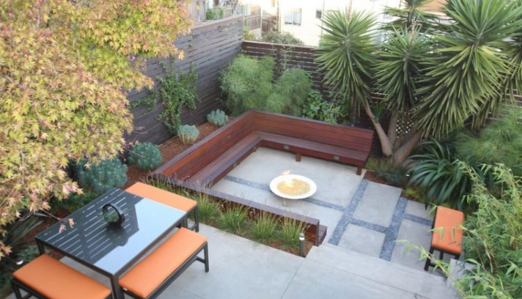 yard with one large seating area at the bottom and one seating are on top surrounded by plants and grey flooring