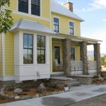 Yellow Farmhouse Exterior With White Framed Windows White Rocking Chairs Exterior Stone Pillars Stone Skirting