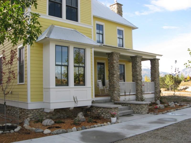 yellow farmhouse exterior with white framed windows white rocking chairs exterior stone pillars stone skirting
