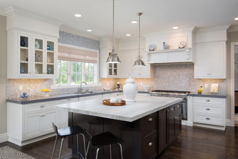 L shaped kitchen idea with grey countertop mosaic tiles backsplash shaker cabinets white cabinets dark wood kitchen island with white top a couple of modern black stools