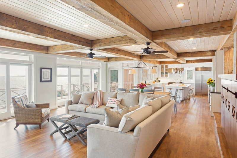 Large beach style open concept living room soft colored soffas rattan coffee table pillow throws hanging lamp standard fireplace, gray walls and light hardwood floors