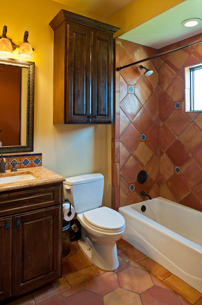 Mediterranean style bathroom terracotta walls and floors wood vanity undermount sink mirror with gold toned frames marble countertop dark wood cabinet over toilet two piece toilet in white white b
