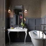Victorian Style Bathroom With Custom Paper Walls Grey Baseboard Herringbone Marble Floors Silver Claw Foot Tub White Vanity Mirror With Metal Frame