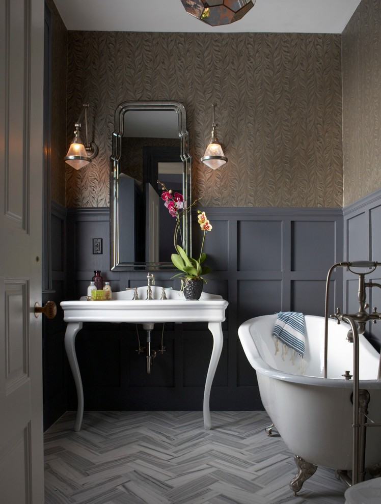 Victorian style bathroom with custom paper walls grey baseboard herringbone marble floors silver claw foot tub white vanity mirror with metal frame