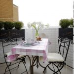 apartment balcony furniture table chairs cloth decorative plants flowers eclectic area
