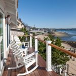 apartment balcony furniture wood floor railing white rocking chairs beach style outdoor area