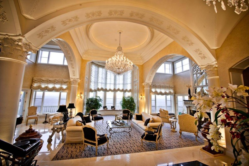 archway floor to ceiling glass window window covering rug area black chairs chandelier decorative ceiling curved table
