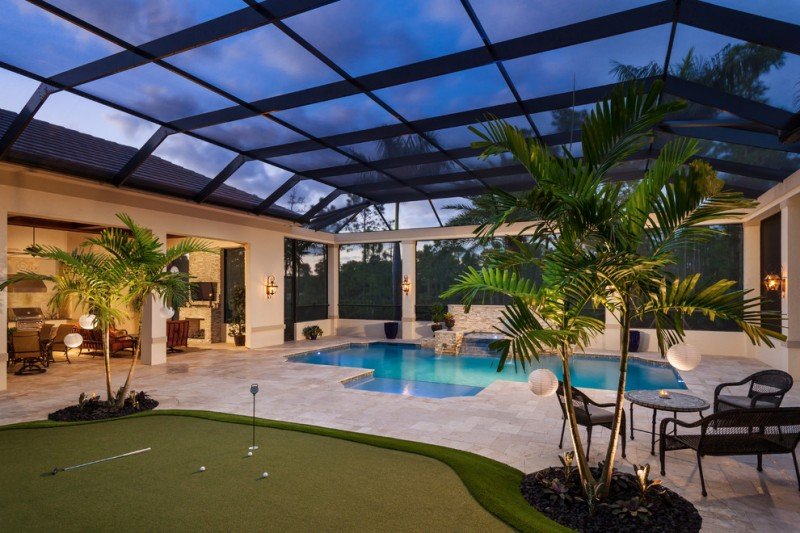 asymmetrical interior pool pale toned paving floors glass enclosure with black aluminum supporters tropical vegetations