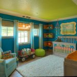 baby crib with blue ribbon cream rug blue painted wall green painted ceiling light blue curtains bamboo shades book storage with wheels
