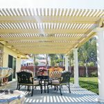 backyard patio covers fountain ornate chairs round table stone pavers flower centerpiece white pillars traditional design