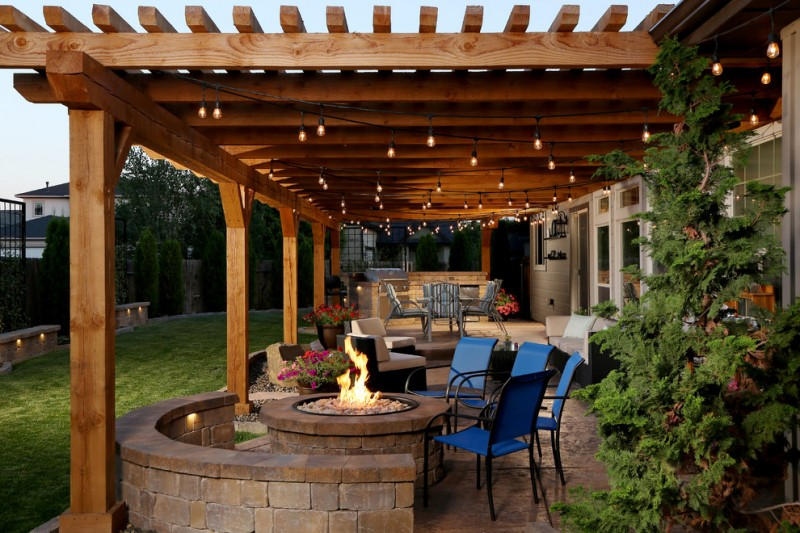 backyard patio covers gas fire pit small chairs stone pavers string lights sofa glass doors decorative trees rustic design