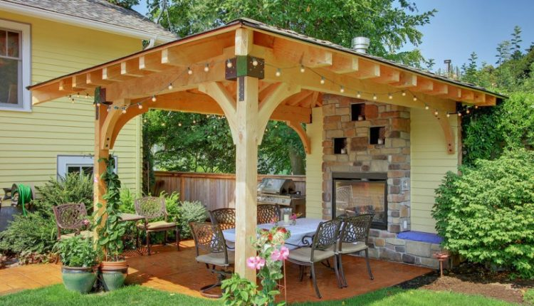 backyard patio covers long table dining chairs string lights outdoor fireplace stone tiles concrete floors beige walls traditional design