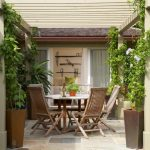 Backyard Patio Covers Wooden Round Table Tall Back Chairs Plant Centerpiece Climbing Vines Wall Decoration Concrete Walls Pots Traditional Design