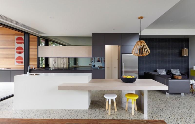 bar style kitchen table flat panel cabinets glass sheet backsplash island sofa stools pendants undermount sink stainless steel appliances marble floors contemporary design