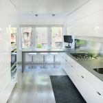 bar style kitchen table quartzite countertop flat panel cabinets undermount sink stools white pendants backsplash stove flat tv concrete floors contemporary design