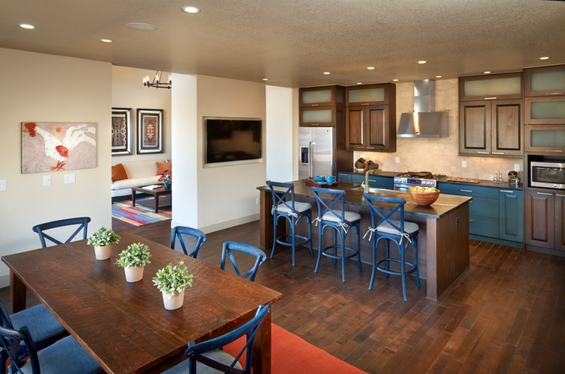 bar style kitchen table raised panel cabinets beige backsplash wood countertops island blue stools ceiling lights stainless steel appliances hardwood floors kitchenette contemporary design